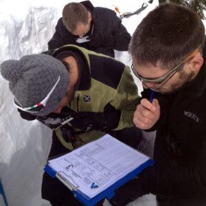 L'analisi dei cristalli con la lente e la tavoletta per redigere il profilo stratigrafico durante il corso di neve e valanghe